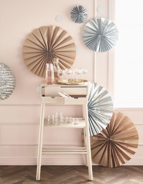Zilverkleurige en bruine rozetten in verschillende formaten hangen aan de muur achter een klein bureau met daarop glazen en met drank gevulde karaffen.