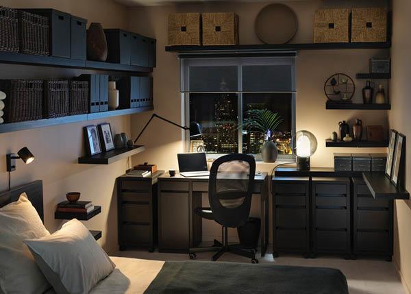 Zimmer mit schwarzem Schreibtisch, Drehstuhl, Tischlampen und Schubladenelementen. An den Wänden sind Wandboards mit Körben angebracht. Ein Bett ist teilweise sichtbar.