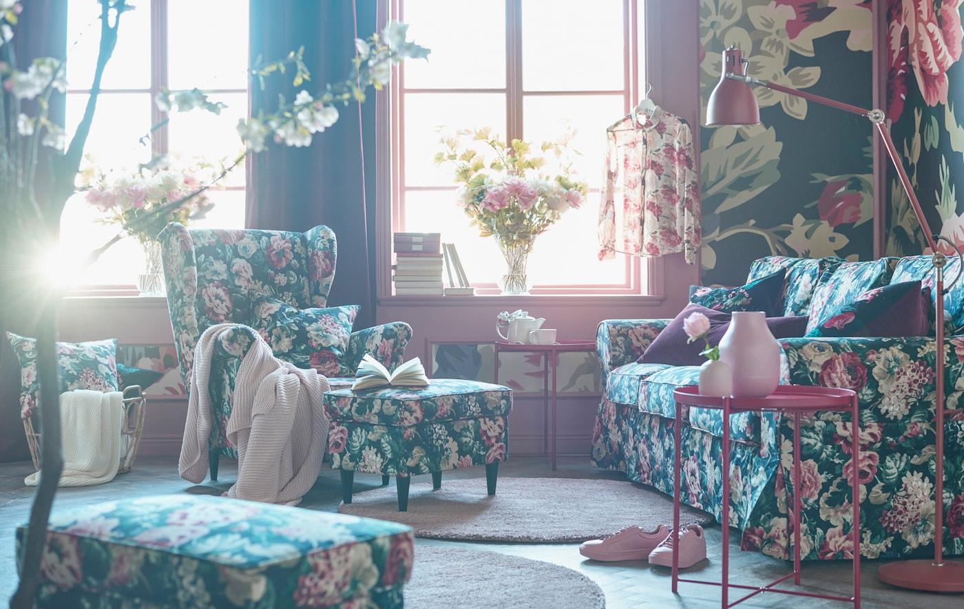 Zitbank met bont bloemenmotief, fauteuil, voetenbank en kussens in een woonkamer met een bont gebloemd behangpapier.
