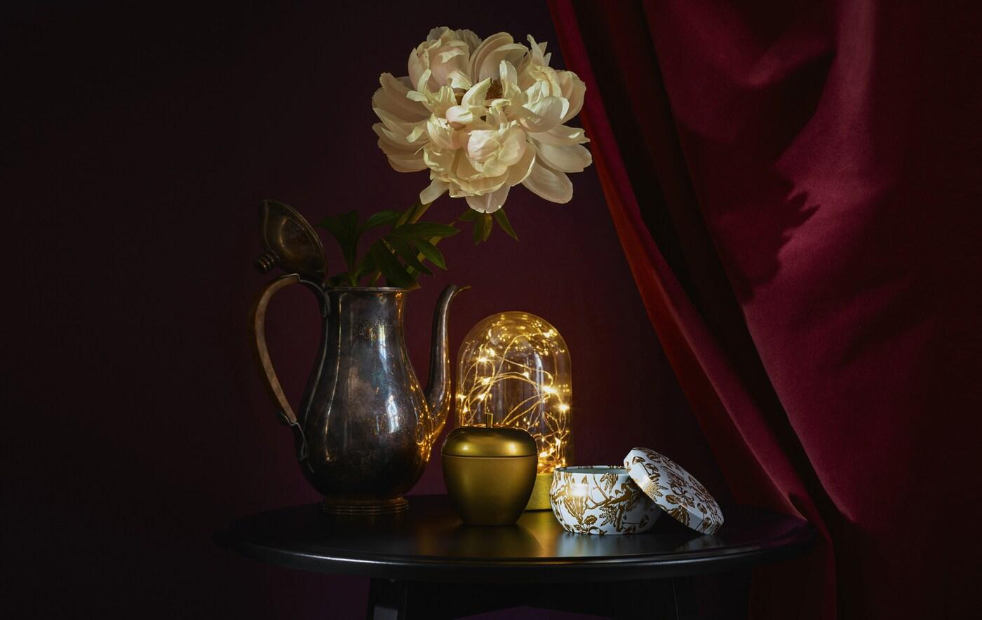 Złote akcesoria i oświetlenie na okrągłym stole na ciemnoczerwonym tle.