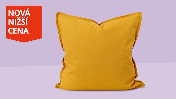 Žlutý polštář na světle fialovém pozadí.