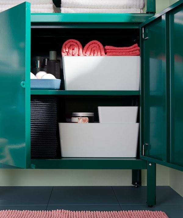 Zöld fémszekrény, nyitott ajtókkal, különféle dobozokkal és kosarakkal.