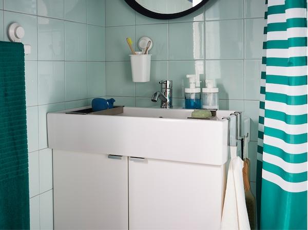 Zöld fürdőszoba, fehér mosdóállvánnyal, törölközőkkel, szappannal és fogkefékkel.