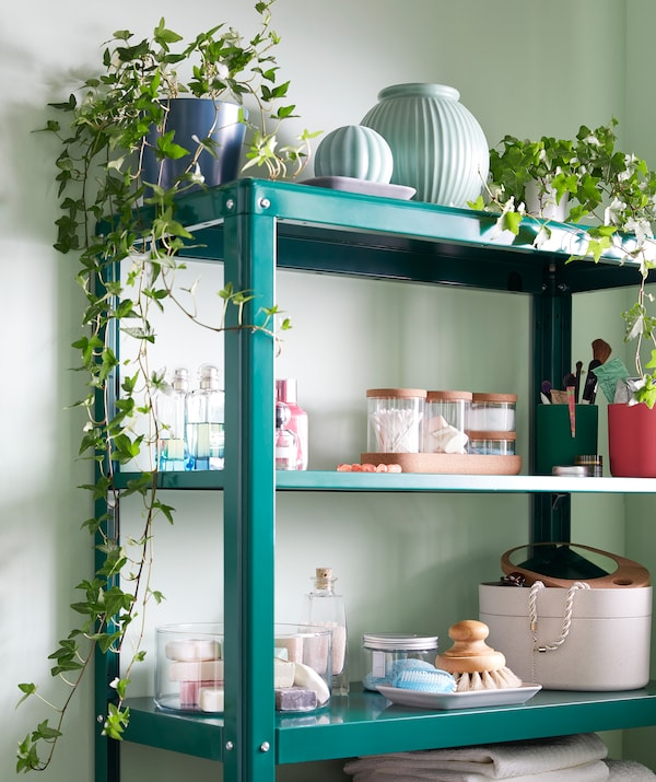 Zöld KOLBJÖRN polc, különféle dekoratív és funkcionális tárolóval: növények, tárolók, fürdőszobai kiegészítők.