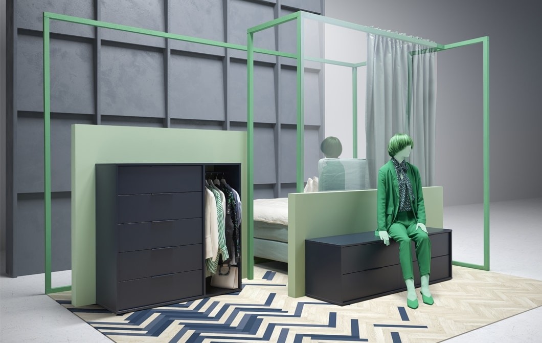 Zöld ruhába öltöztetett figura ül egy alacsony ládán, egy magasabb fiókos szekrény mellett.