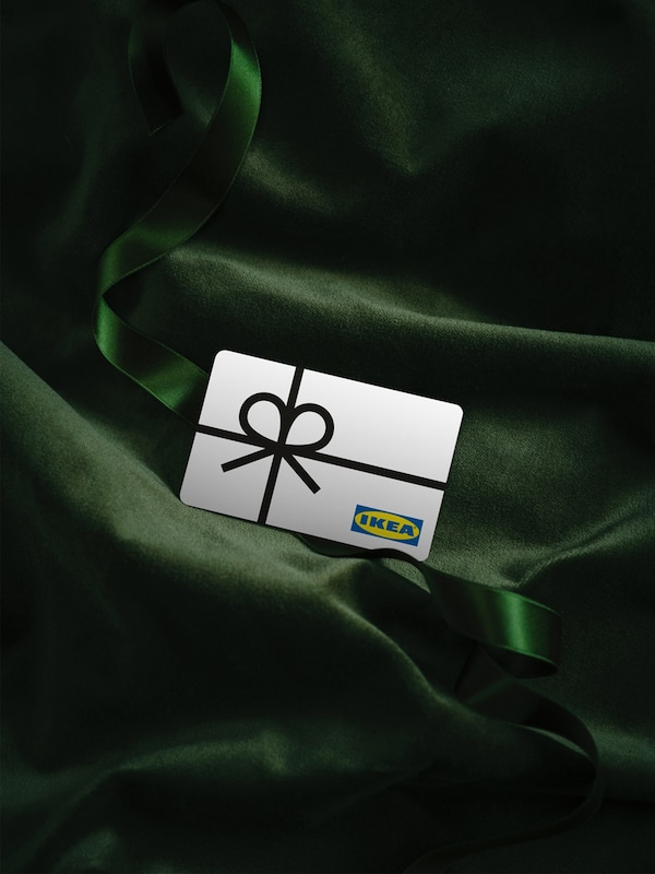 Zöld selyem háttéren IKEA ajándékkártya fekszik.