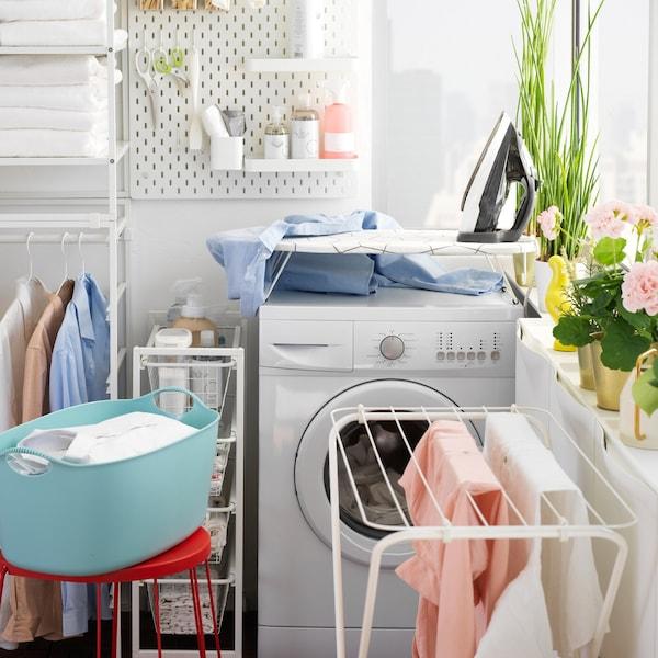 Zona de bogada con táboa pequena de pasar o ferro JÄLL colocada enriba dunha lavadora e bogada tendida para secar nun bastidor branco.