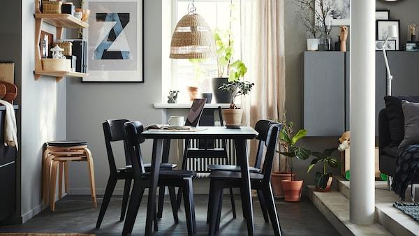 Zonă de servit masa, cu o masă, patru scaune și un scaun înalt negru, etajere deschise cu furnir cenușiu, patru taburete și draperii bej.