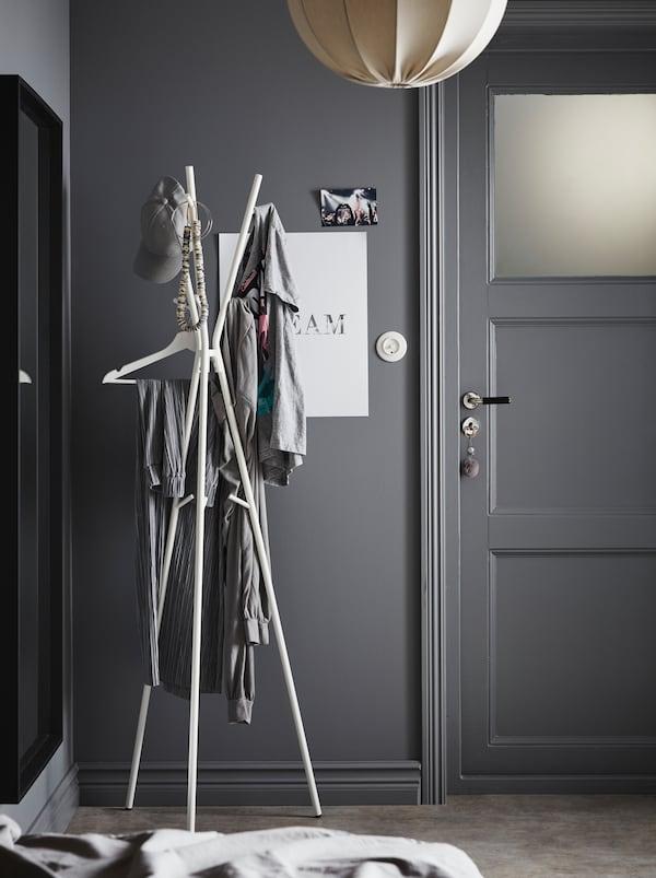 Zona holului într-o schemă de nuanțe de gri. În fața ușii se află un cuier de pălării și haine EKRAR pe care se află diferite obiecte de îmbrăcăminte.