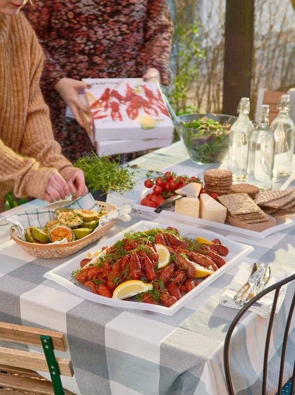 Zonovergoten tafel gedekt voor een feestje met een berg KRÄFTOR rivierkreeftjes op één SMULA dienblad en kaas en crackers op een ander dienblad.