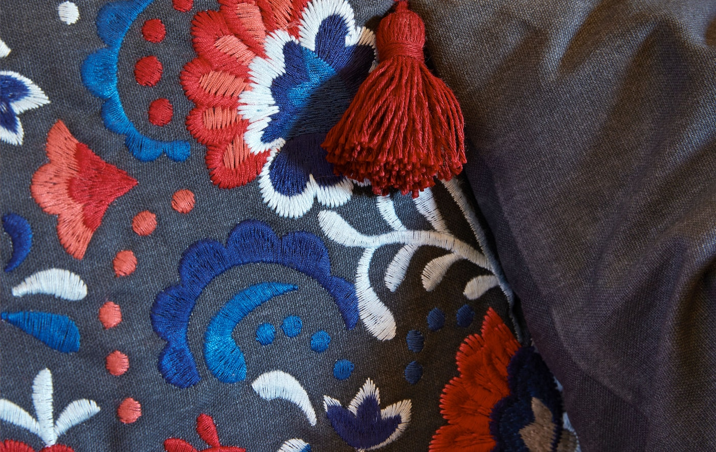 Zoomed-in section of a cushion cover, embroidered with intricate, different-colour patterns, a tassel hanging from a corner.