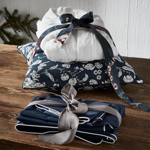 Župan a polštář převázaný mašlí, před ním na stole leží ručník převázaný stužkou.