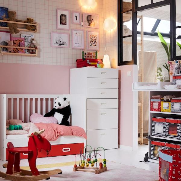 Zuri-koloreko IKEA STUVA sehaska eta sei tiraderetako modulua jostailuak eta peluxezko panda bat dituen haurtxoentzako logelan.