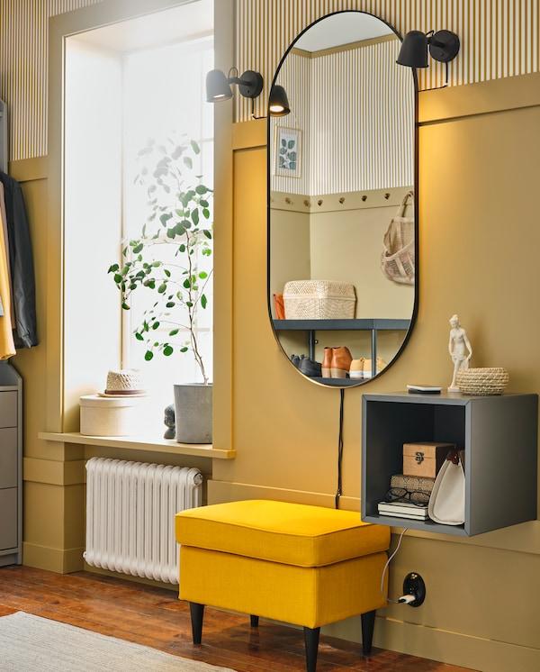 Žuti zid na kojem se nalazi ovalno ogledalo, dve crne lampe i tamnosivi zidni ormarić. Žuta stoličica smeštena je ispod ogledala.