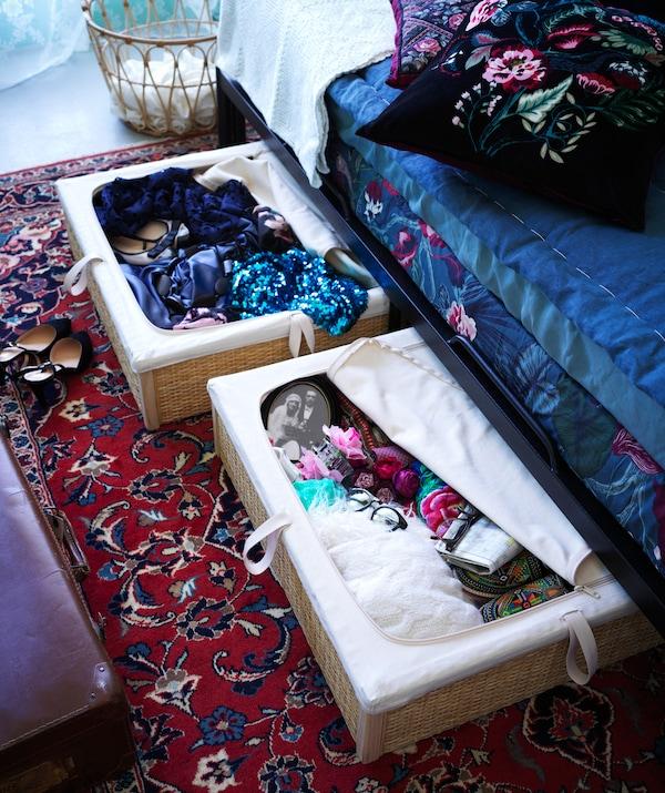 Zwei ausgezogene, gefüllte Aufbewahrungsboxen aus Rattan unter einem Tagesbett