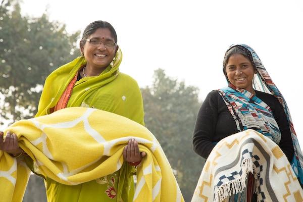 Zwei Frauen halten handgewebte Teppiche in ihren Händen.