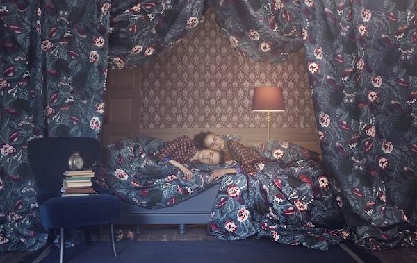 Zwei Frauen liegen auf einem Bett in geblümter Bettwäsche vor einer gemusterten Tapete.