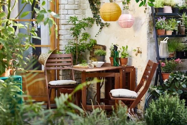Zwei Gartenstühle mit Kissen an einem Gartentisch vor einem Regal mit Blumentöpfen