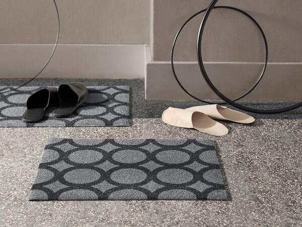 Zwei graue IKEA MEJLS Fußmatten mit einem runden Muster in Schwarz. Die Matten sind aus recycelten PET-Flaschen gefertigt.