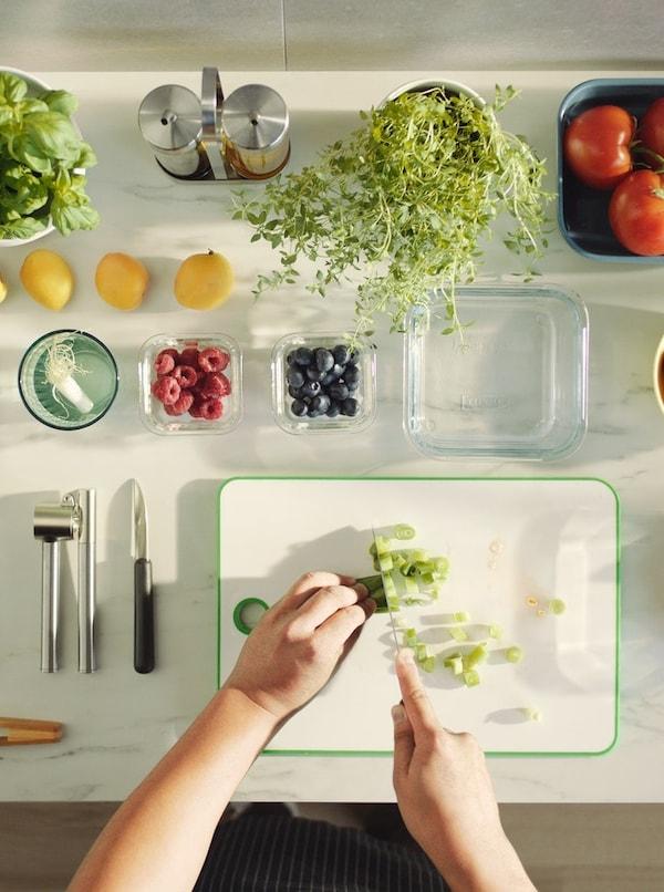 Zwei Hände schneiden Gemüse auf einer Arbeitsfläche, auf der Utensilien, Behälter und Gemüse rechtwinklig angeordnet sind.