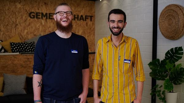 Zwei IKEA Auszubildende vor einer Wand Gemeinschaft