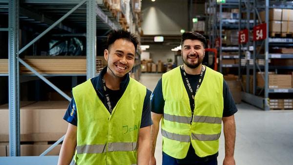 Zwei IKEA Lehrlinge zum Betriebslogistikkaufmann stehen nebeneinander im Lager und haben Spaß an der Arbeit