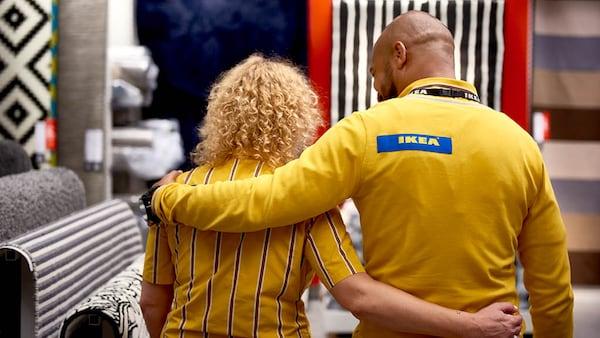 Zwei IKEA Mitarbeiter gehen Arm in Arm mit dem Rücken zur Kamera durch den Store.
