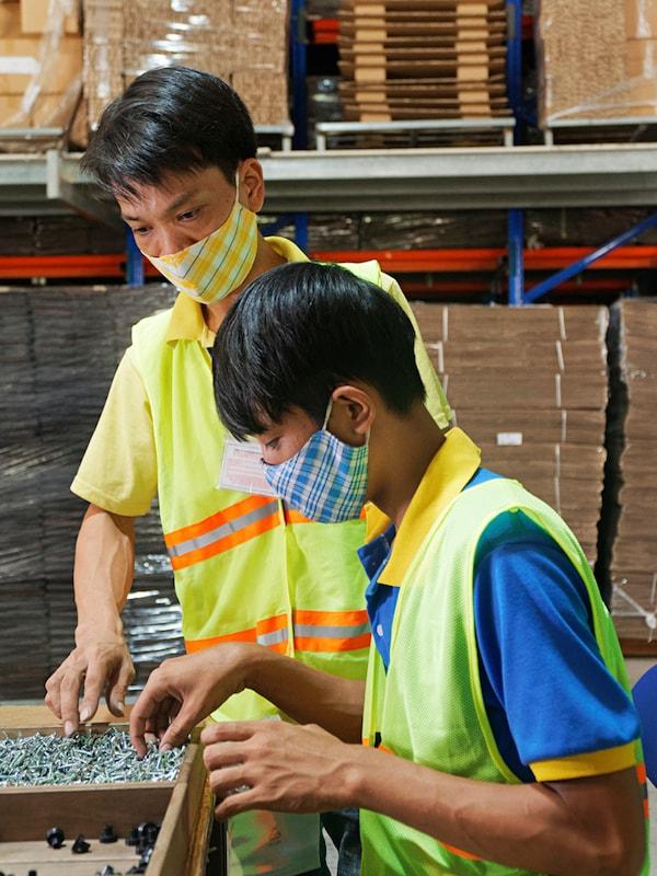 Zwei IKEA Mitarbeiter tragen gelbe Sicherheitswesten und Masken. Sie inspizieren Schrauben in einer Fabrik.
