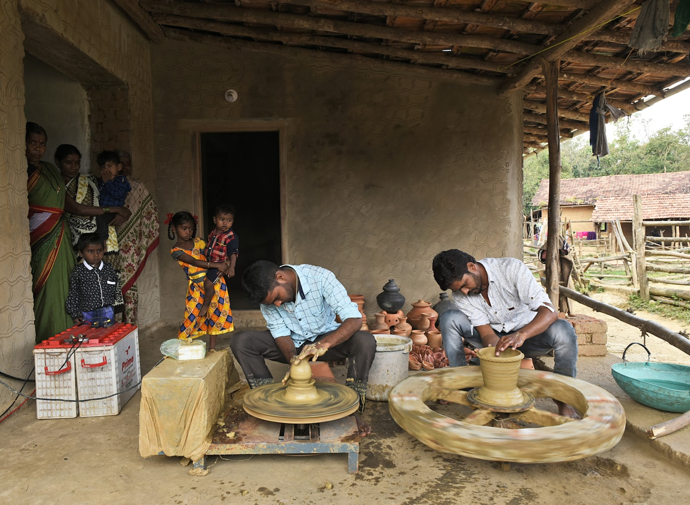 Zwei indische Töpfer arbeiten an ihren Drehscheiben. Um sie herum stehen Dorfbewohner, die sie beobachten.