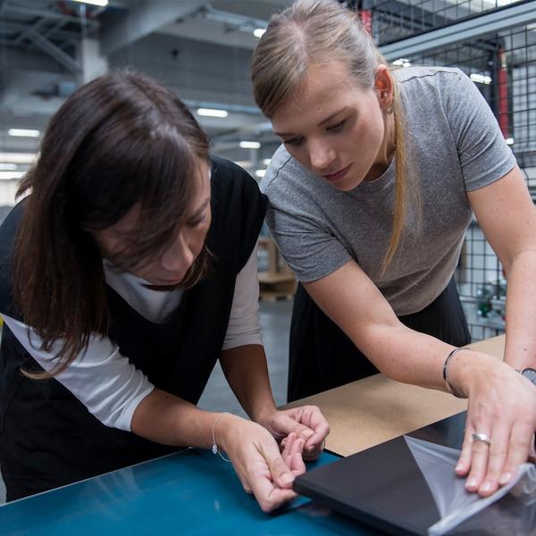 Zwei junge IKEA Produktentwicklerinnen untersuchen ein Produkt, das sich noch in der Entwicklungsphase befindet.