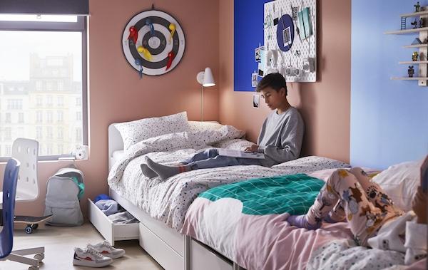 Zwei Kinder auf SLÄKT Bettgestellen, Unterbett+Aufbewahrung weiß, die Fußende an Fußende stehen in einem Raum in Rosa und Korallenrot.