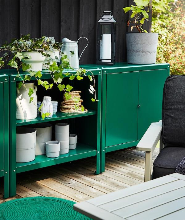 Zwei KOLBJÖRN Schränke für drinnen und draußen in Grün auf einer Terrasse. Darauf sind Pflanzen zu sehen.