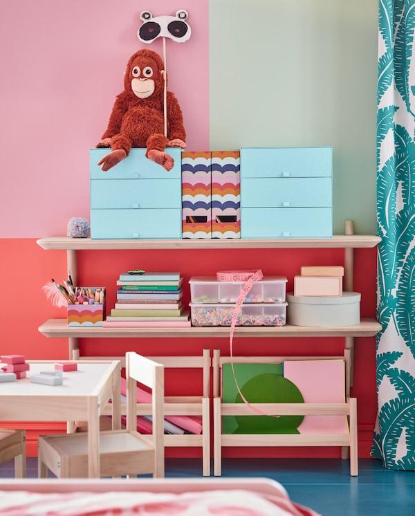 Zwei LISABO Wandregale aus Eschenfurnier, auf denen Boxen, ein Stoffspielzeug, Bücher und Bastelprojekte zu sehen sind.