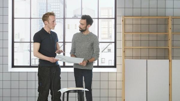Zwei Männer besprechen in einem weiss gefliessten Raum einen Installationsplan für den weiteren Umbau
