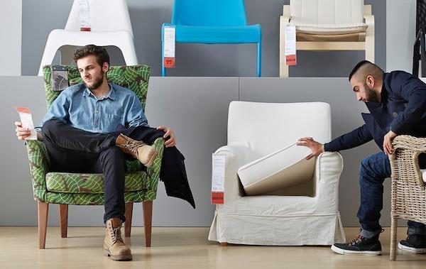 Zwei Männer sitzen in Sesseln im Wohnzimmerbereich in einem IKEA Einrichtungshaus. Einer sieht sich das Preisschild an, der andere nimmt das Sitzpolster genauer unter die Lupe.