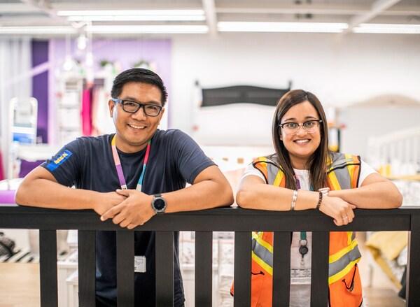 Zwei Personen in IKEA Mitarbeiteruniformen lehnen an einem Holzgestell. Beide tragen IKEA Schlüsselanhänger und lächeln.