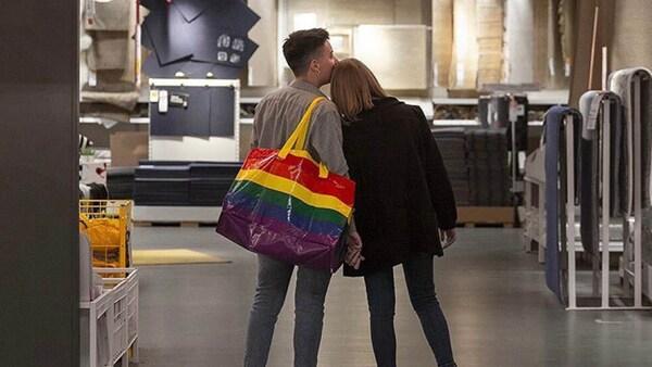 Zwei Personen mit einer Regenbögentasche beim Shoppen