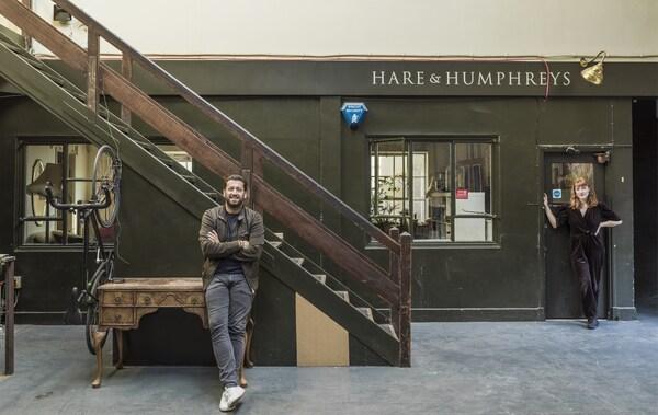 Zwei Personen stehen vor einem alten Geschäft und einem Treppenaufgang.