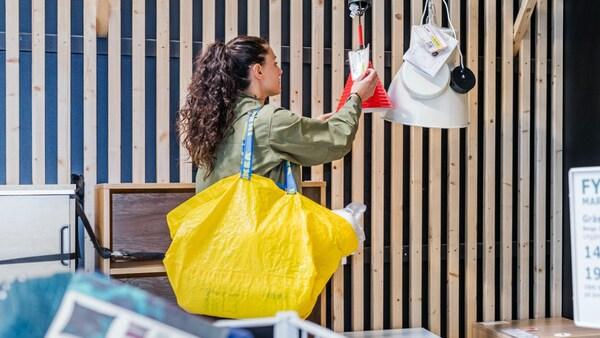 Zwei Personen tragen ein weißes KALLAX Regal aus dem Circular Hub bei IKEA über die Straße