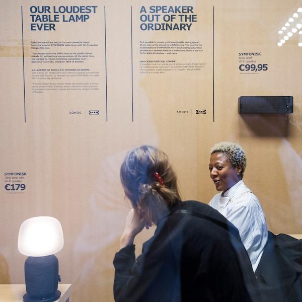 Zwei Personen unterhalten sich neben einer IKEA SYMFONISK Tischleuchte mit Lautsprecher. Im Hintergrund ist ein grafisches Poster zu sehen.