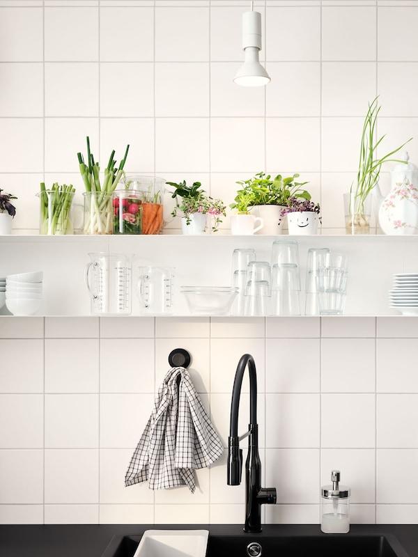 Zwei Regale mit Glasbehältern und Gemüselebensmittelresten hängen über einer schwarzen Arbeitsplatte mit einer schwarzen Mischbatterie.