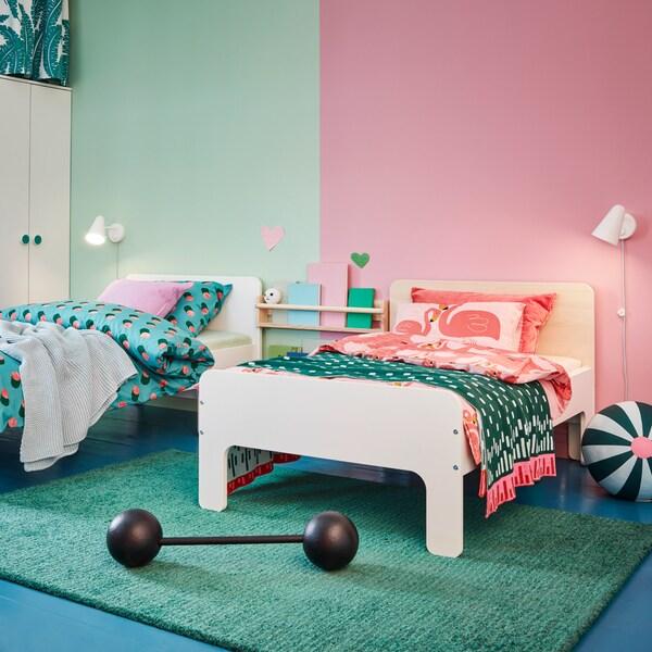 Zwei SLÄKT ausziehbare Bettgestelle mit unterschiedlich gestalteten Kopfteilen: eines ist weiß, das andere birkenfarben. Beide sind mit bunter Bettwäsche bezogen.
