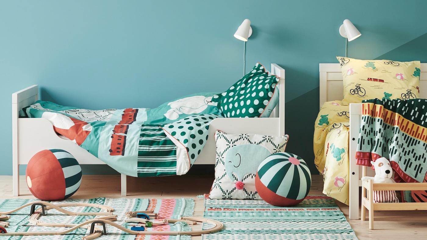 Zwei SUNDVIK Bettgestelle mit der KÄPPHÄST Bettwäsche stehen in einem Zimmer rechtwinklig zueinander. Auf dem Boden sind Spielzeug und ein Kissen zu sehen.