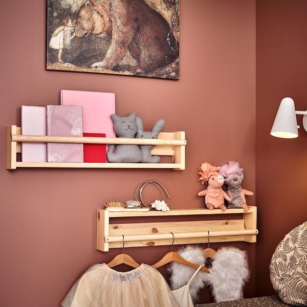 Zwei Wandaufbewahrungen in massiver Kiefer hängen an einer Wand in Rosa. In einer befinden sich Bücher, die andere ist umgedreht angebracht. An ihr hängt Kleidung.