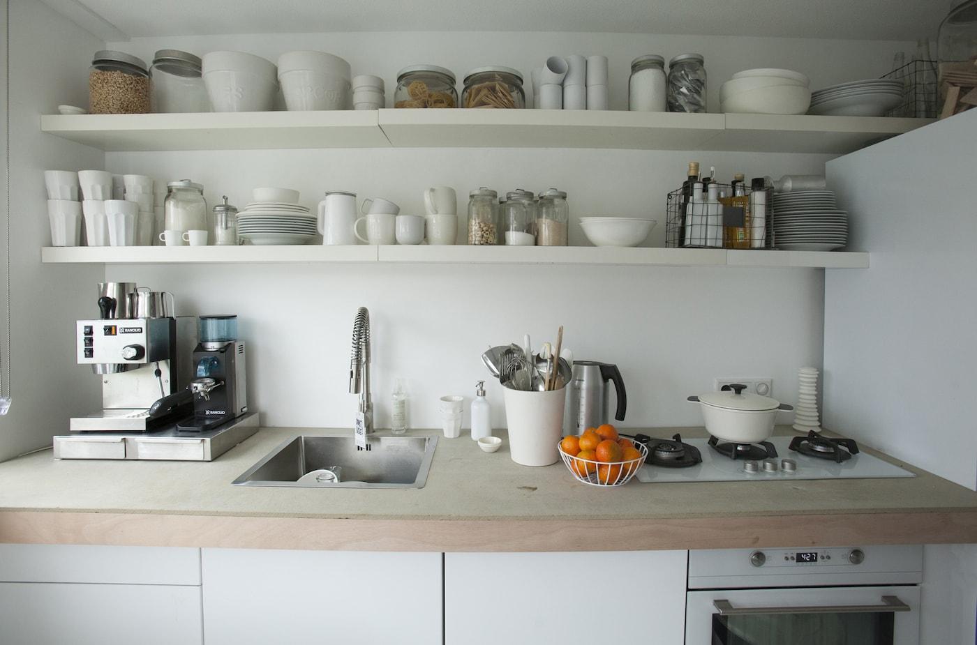 Zwei weiße Regale voll Geschirr über einer hölzernen Arbeitsfläche einer Küche mit weißen Schränken & vielen Kochutensilien.