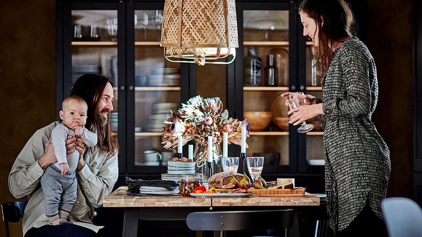 زوجان مع طفل مجتمعون حول طاولة طعام. خزائن بأبواب زجاجية داكنة مع إكسسوارات طاولة بجانب الجدار البعيد.