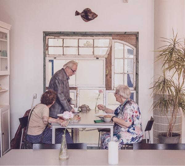 زوجان مسنان وصديق لهما يتناولان الغداء معًا في مطعم مميز.