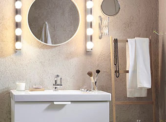 A bathroom sink and black cabinet, mirror cabinet and long white cupboard in a white-tiled room.