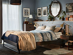 A dark brown and light blue bedroom with TRYSIL bed, bedside table, wardrobe and chest of 4 drawers.