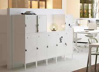 White HÄLLAN cabinets displayed in a contemporary working environment.